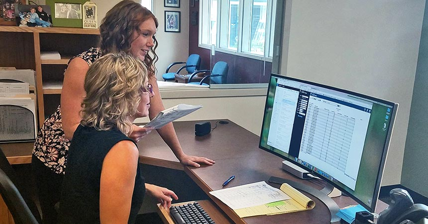 Commercial SEM intern Cacey Thomas and facilities support supervisor Anne Birky working on the energy management database for Bend-La Pine School District.