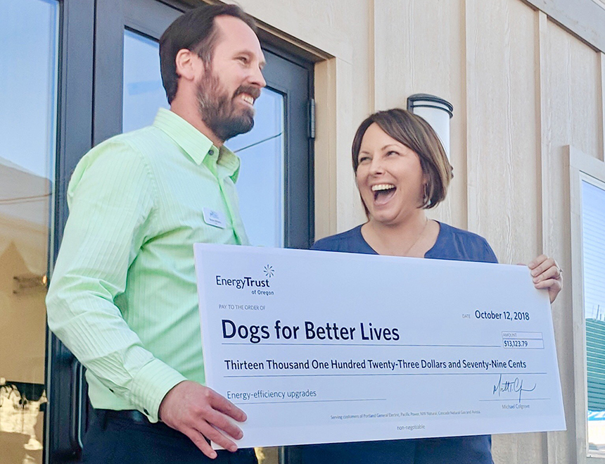 two people holding a big incentive check for Dogs for Better Lives