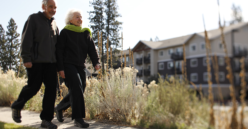 two seniors walking on a crisp fall day in front of a retirement center