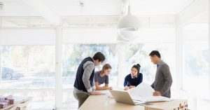 four people examing blue prints in a room filled with natural light