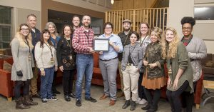 Employees of Energy Trust of Oregon and Shepherd's Door pose with a certificate honoring solar energy upgrades made to the Shepherd's Door facility in Northeast Portland, November 28, 2018.