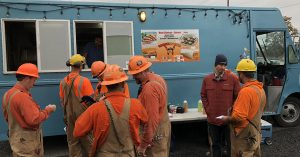 construction workers outside of a taco truck