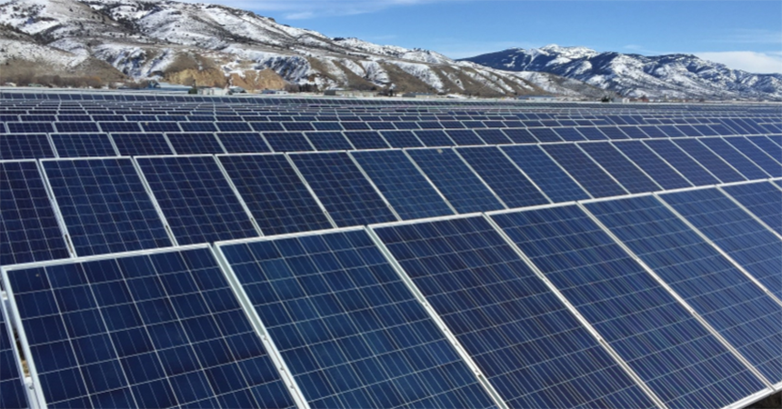 a solar array with snowy mountains in the background