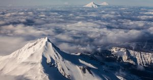snow covered mountain peak above the clouds