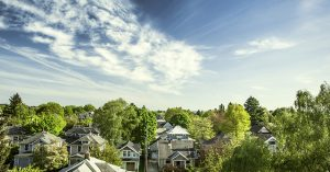 """Portland Oregon's east-side """"suburbs"""" on a warm summer day, a vibrant blue sky and clouds over neighborhood houses and green trees. Horizontal with copy space."""
