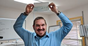 A smiling man holds up a check with his incentive