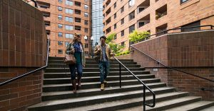 a man and a woman walking in front of a nice multifamily building