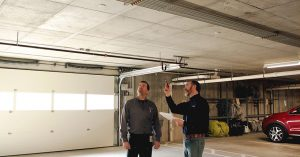 a technician and a property manager in a parking garage inspecting the lighting