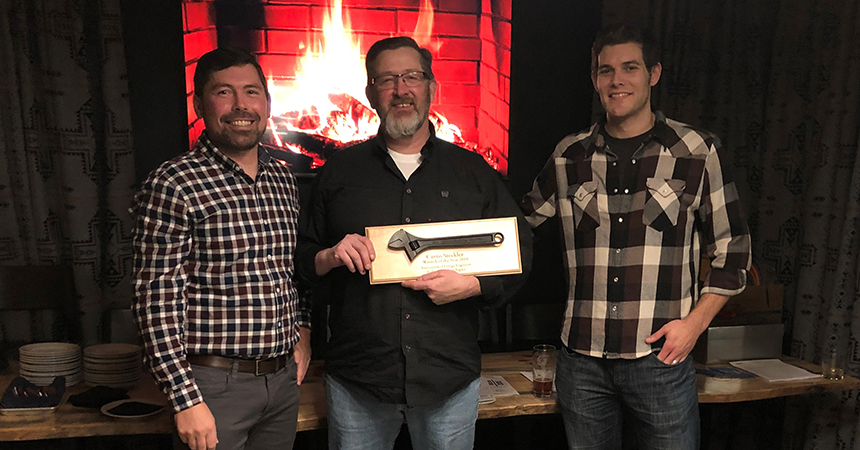 Two men stand next to the 2018 Wrench of the Year winner, Curtis Steckler.