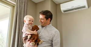 a man and his son in front of a ductless heat pump