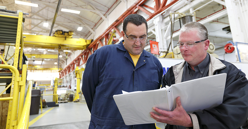 Two men overviewing documents in a well lit warehouse