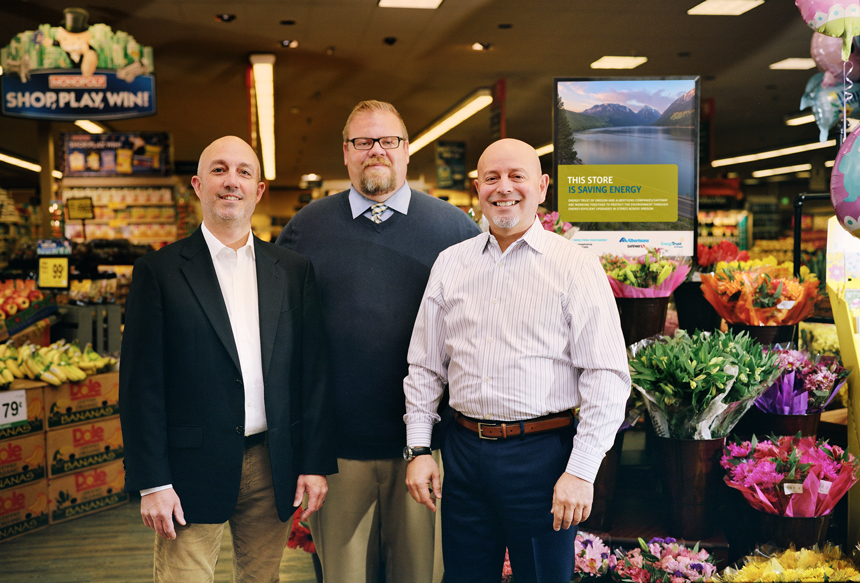 Energy Trust and Alberstons Companies representatives standing in front of flowers and produce at Woodstock Safeway in Portland.