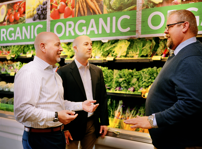 Albertsons Companies corporate energy manager, Victor Muñoz, discusses refrigeration improvements with Energy Trust account manager, Alex Inman, and Ecology Action VP of Innovation, John Peterson, in the produce section of the Woodstock Safeway in Portland.