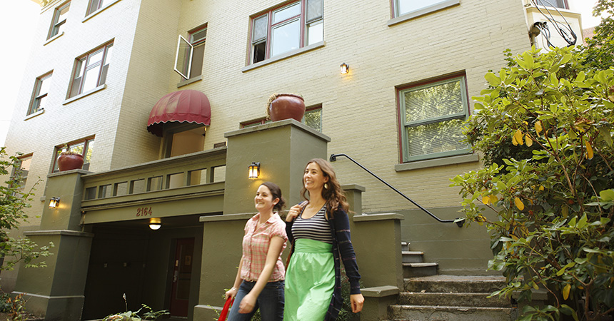 two women walking out of their appartment building