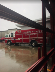 a firetruck in a rain covered lot outside a new building