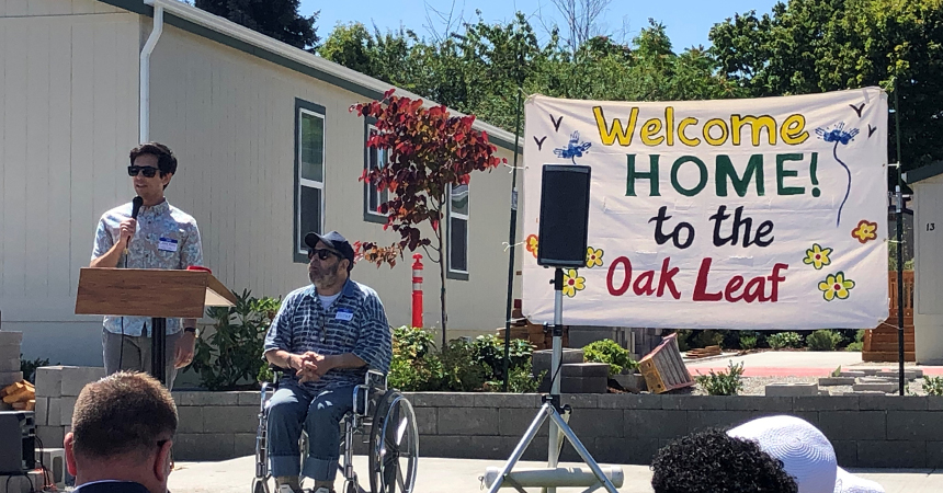 a welcome home to oak leaf banner with a man at a podium and a man in a wheelchair addressing a crowd