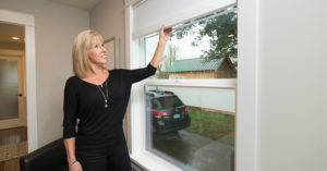 a woman smiling, closing her energy efficient windows
