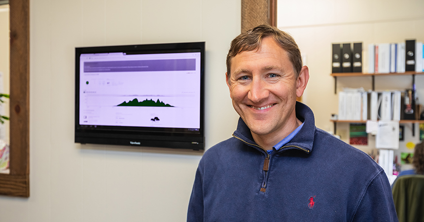 a man smiling in front of a display showing energy savings