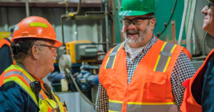 three men in bright orange vests and construction hats conversing and smiling