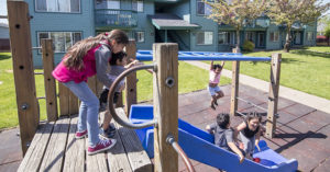 children playing on a play set outside of a green apartment building