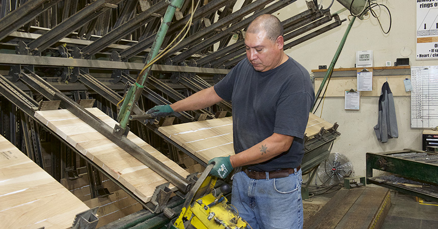 a person with a shaved head cutting lumber in a factory setting
