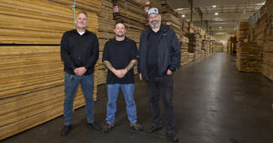 three men standing among rows and rows of lumber
