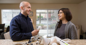 two people looking over energy efficient lightbulbs and water saving devices
