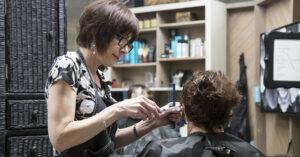 Beth Koblegarde cuts the hair of Carol Sutton at Shears Ahead salon, Tigard, Oregon, April 15, 2019.