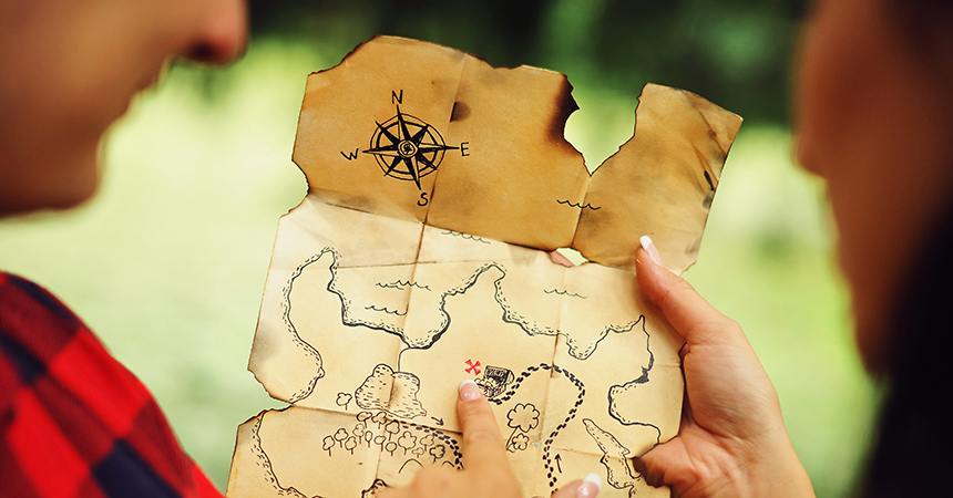 Couple of lovers holding a pirate map in hands and looking for treasures. Romantic quest journey concept. Love story