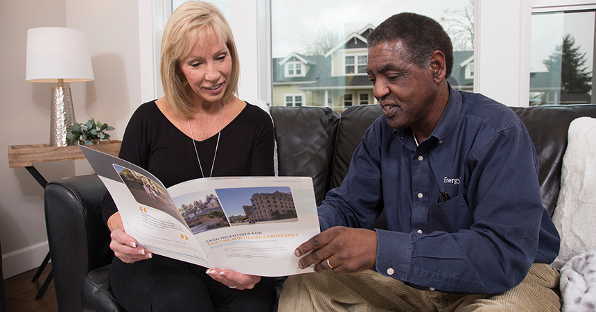 a man and woman looking at a pamphlet on a couch