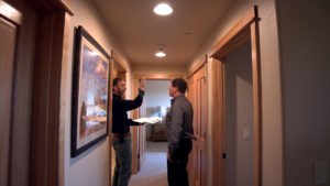Contractor with customer in hallway talking about lighting.