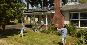 Family playing catch in front of house with solar panels