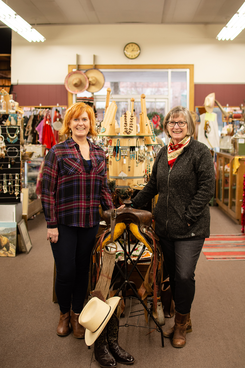 two women standing next to a saddle