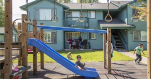 a multifamily building with children playing outside