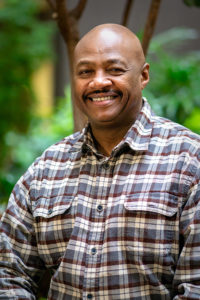 tyrone henry smiling in front of greenery