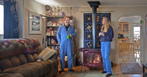 a man and woman in a cozy living room with a fireplace