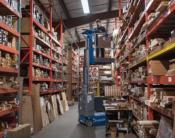a man on a forklift in a warehouse of lumber