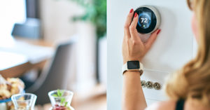 a woman adjusting a smart thermostat