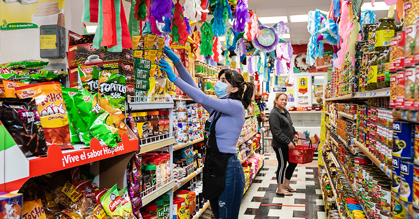 a woman in a mask stocking a grocery store shelf