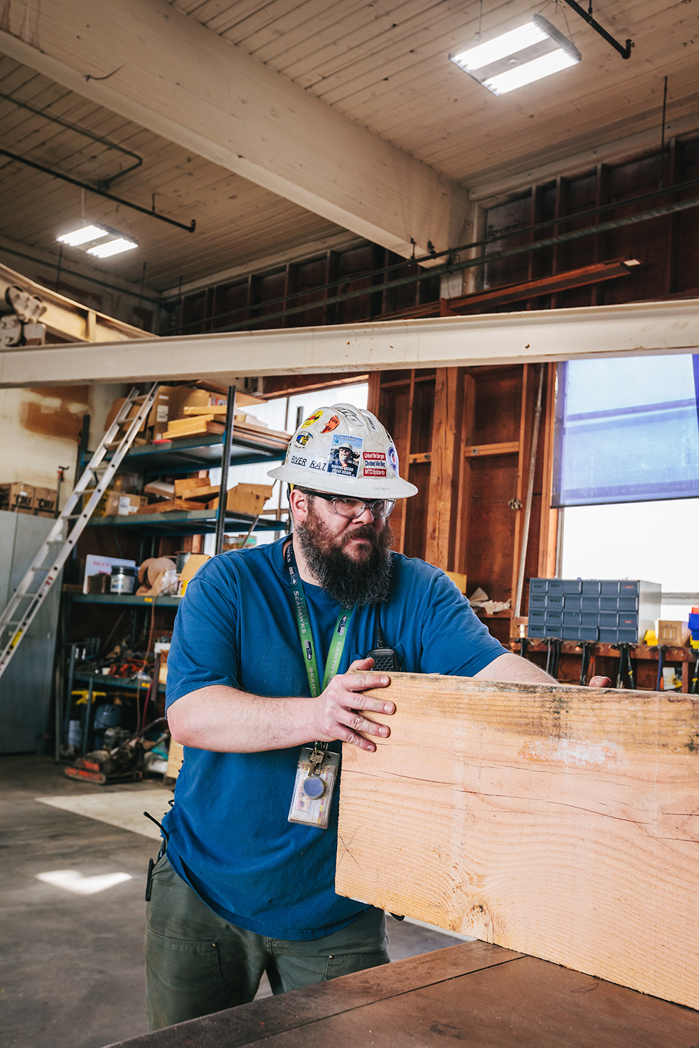 a bearded man in a hard hat moving lumber