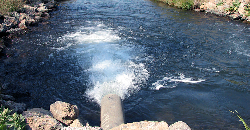 water flowing out of an irrigation pipe into a channel