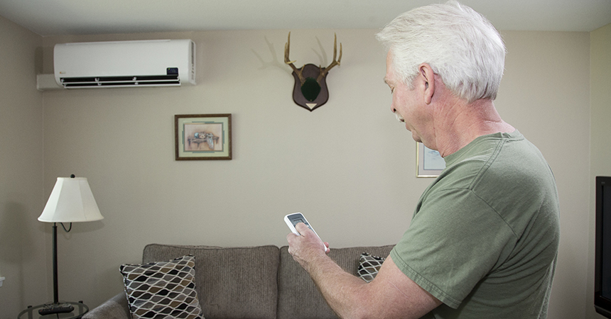 a man with white hair adjusting his heat pump with a remote control