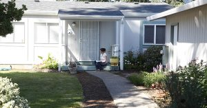 a woman sitting on a porch of a house