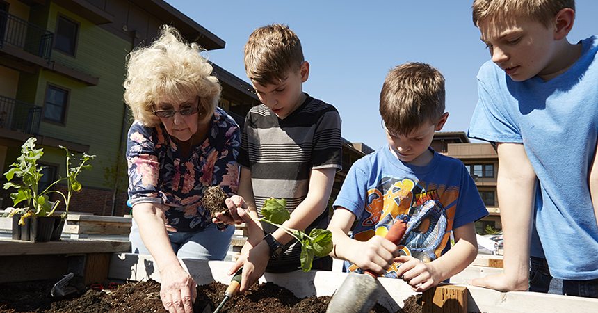 a woman and 3 children planting things in a garden